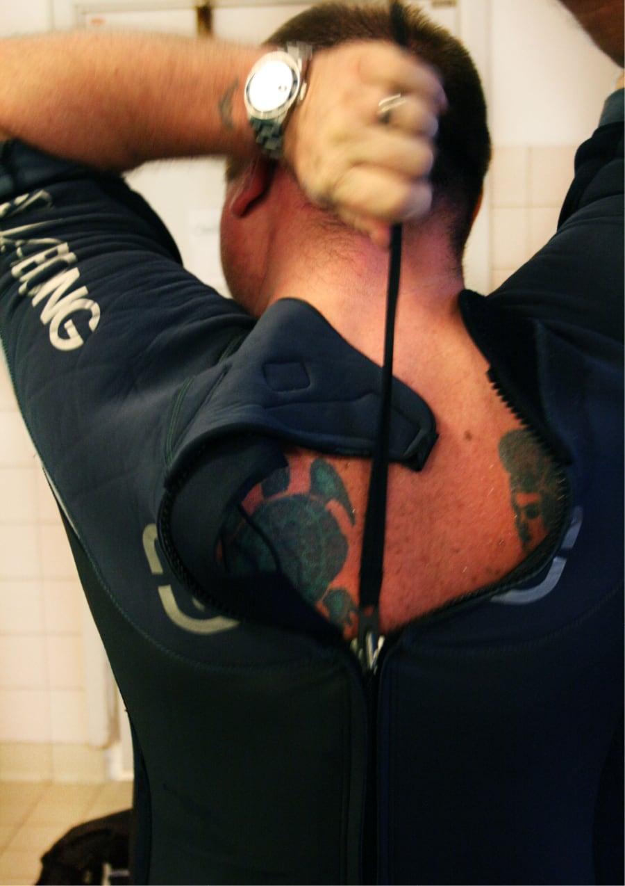 Dykare drar upp dragkedja på ryggen