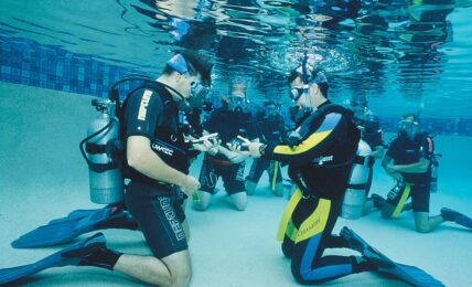 Dykträning i grupp fotade under vatten i bassäng